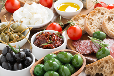 A spread of olives cheeses and meats